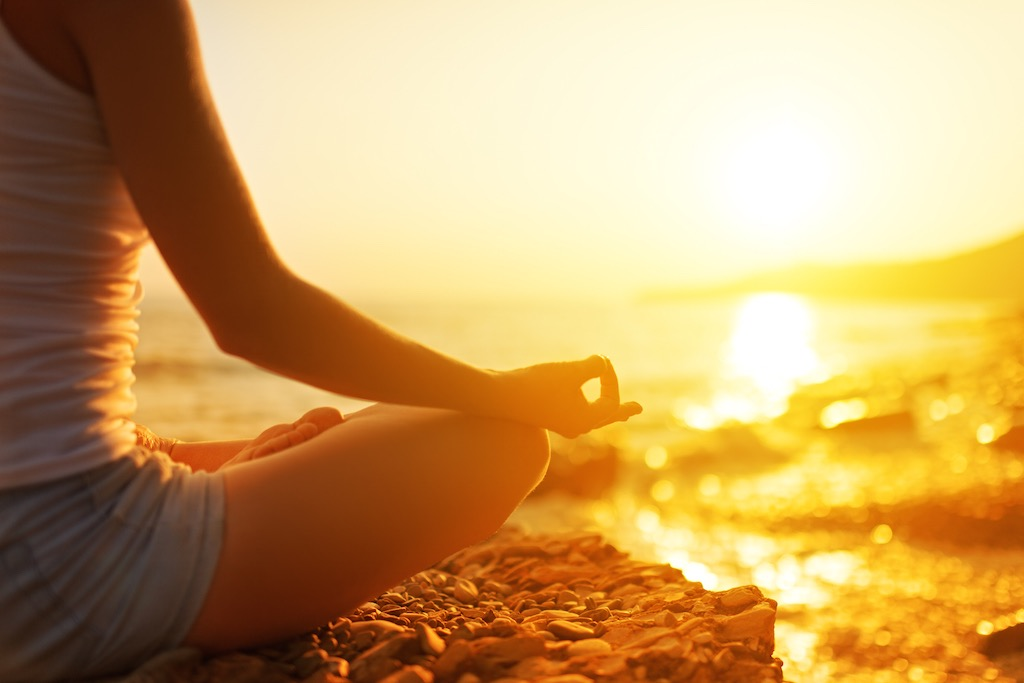 Hand ff Woman Meditating in a Yoga Pose on Beach